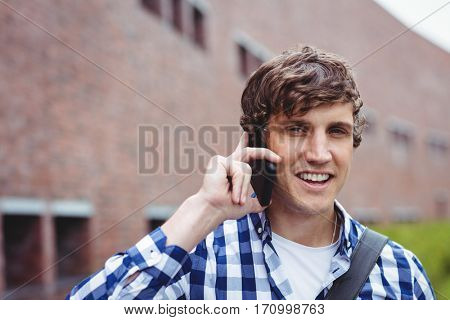 Portrait of smiling student talking on mobile phone in college campus