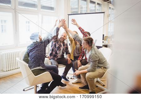 Happy creative business people giving high-five in meeting room at creative office