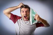 young crazy desperate and frustrated man doing housework holding iron against his face and cable stressed and confused in unskilled and unable male for ironing isolated on even background poster