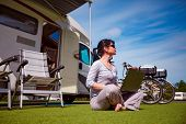 Woman on the grass, looking at the laptop near the camping . Caravan car Vacation. Family vacation travel, holiday trip in motorhome poster