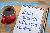 Build authority with your content , blogging tip - handwriting in a spiral notebook with a cup of coffee poster