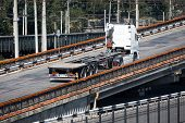 one white truck on road rides up over the bridge, industrial infrastructure, cargo transportation, delivery and shipping concept poster