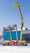 Vertical panorama of the three different self propelled wheeled hydraulic articulated boom lift with telescoping booms and baskets against the sky and an industrial building in winter sunny day poster