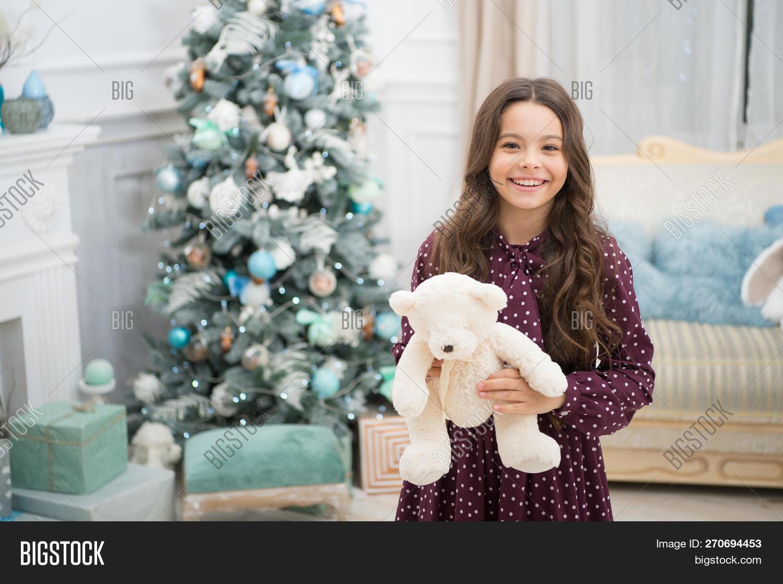 20473bd2eb Teddy bear improve psychological wellbeing. Child small girl playful hold  teddy bear plush toy. Kid little girl play toy teddy bear christmas tree ...