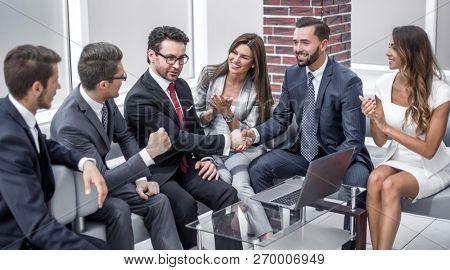 business team applauding business partners at an informal meeting.