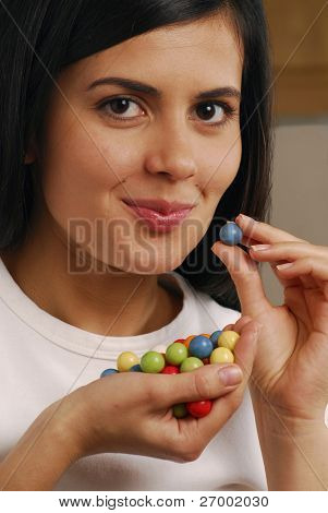 Young woman eating candies.