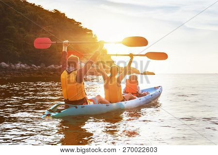 Happy Family Is Walking At Sunset Sea By Kayak Or Canoe. Active Tourism Concept