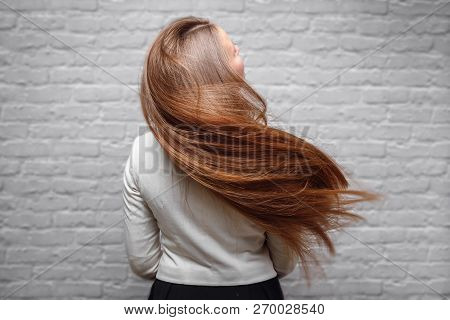 Portrait Of Beautiful Young Brunette Woman With Long Straight Loss Hair In Flight Air.