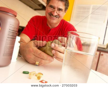 Mid adult man getting his pills in a kitchen.