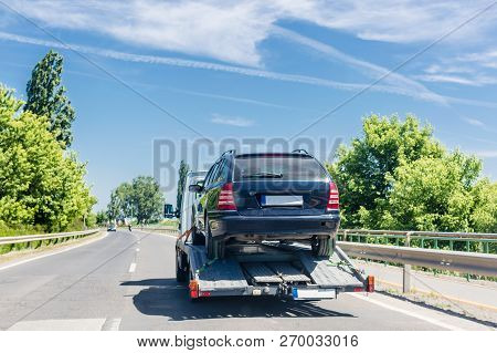 Car Carrier Trailer With Car. Car Transported On Evacuation Tow Truck On Highway