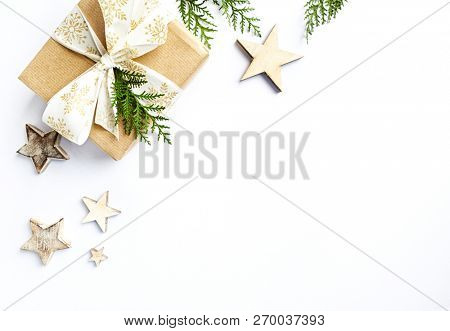 Christmas present with rustic decorations and evergreen twigs. Flatlay. Copy space. White background