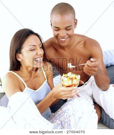 Young hispanic couple enjoying and eating fruit salad on bed.
