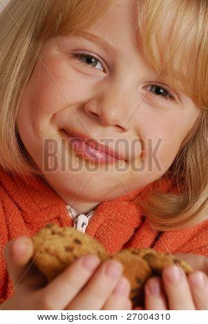 Little girl eating cookies,kid holding cookies.
