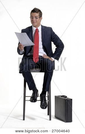 Young businessman sitting on a chair and reading on white background.