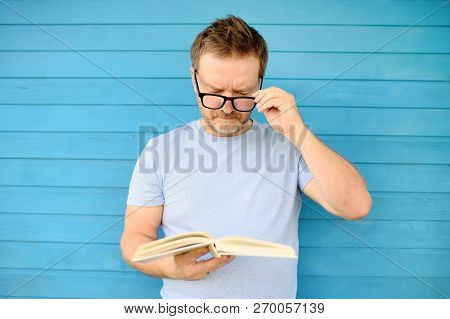 Portrait Of Mature Man With Big Black Eye Glasses Trying To Read Book But Having Difficulties Seeing