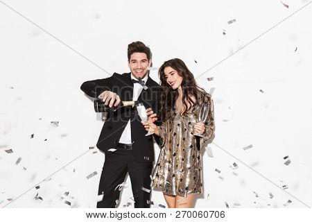 Cheerful young smartly dressed couple celebrating New Year party isolated over white background, drinking sparkling champagne