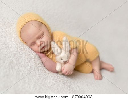 Little baby weared in cute yellow knitted suit sweetly sleeping on the white soft bedcover