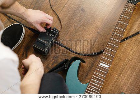 Man Adjusting Guitar Effects Pedal