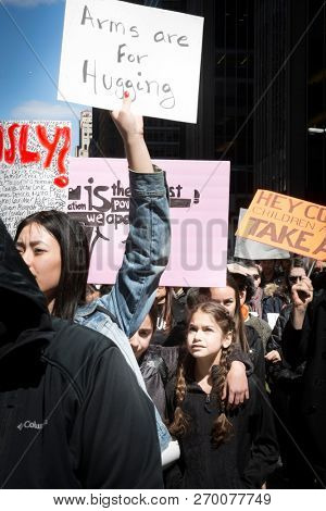 March For Our Lives: A young girl looks up at a protester holding a sign that says Arms Are For Hugging at the march on 6th Ave to end gun violence, NEW YORK MAR 24 2018.