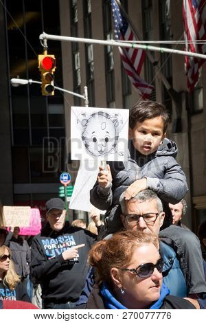 March For Our Lives: A little boy sits on a mans shoulders holding a sign with a baby tiger on it at the protest and national march to end gun violence, 6th Ave NEW YORK MAR 24 2018.