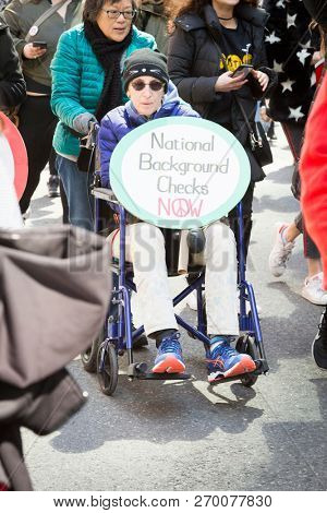 March For Our Lives: A protester in a wheelchair holds a sign that say National Background Checks Now at the march on 6th Ave to end gun violence, NEW YORK MAR 24 2018.