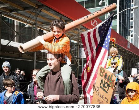 March For Our Lives: A young boy sitting on a mans shoulders carries a large American Flag attached to a cardboard tube at the march on 6th Ave to end gun violence, NEW YORK MAR 24 2018.