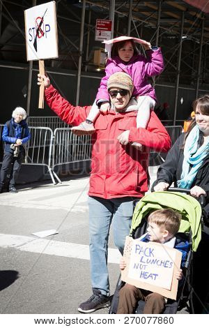 March For Our Lives: A man holding a little girl on his shoulders protests at the national march to end gun violence, 6th Ave NEW YORK MAR 24 2018.