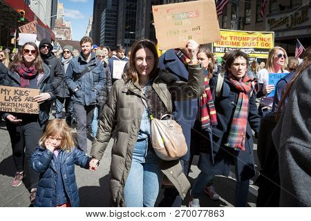 March For Our Lives: A little girl sucking her thumb walks with her mom who holds  a sign that says No More Guns at the national march to end gun violence, 6th Ave NEW YORK MAR 24 2018.