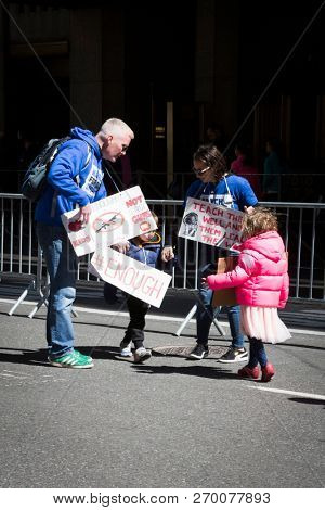 March For Our Lives: A little girl and boy with their family and protest signs participate in the national march to end gun violence, 6th Ave NEW YORK MAR 24 2018.