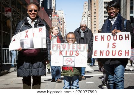 March For Our Lives: A little boy holding a sign that says Protect Kids Not Guns walks with adults at the national march to end gun violence, 6th Ave NEW YORK MAR 24 2018.
