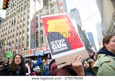 March For Our Lives: Close up of a protester holding a sign that says Stop Gun Violence with an illustration of President Donald Trump at the march to end gun violence on 6th Ave NEW YORK MAR 24 2018.