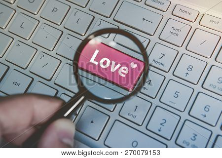 Written Word Love On Keyboard Red Button Viewed Through The Magnifying Glass. Close Up Of Male Hand