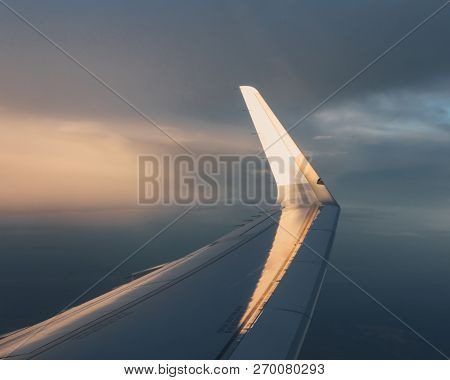 wing of airplane with sunlight on winglet