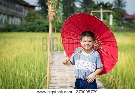 Little asian boy smile and hold pink umbrella selective focus with copy space.