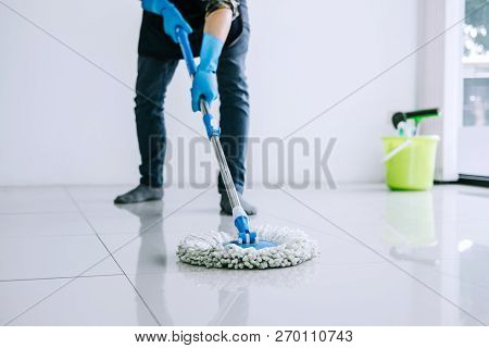 Husband Housekeeping And Cleaning Concept, Happy Young Man In Blue Rubber Gloves Wiping Dust Using M