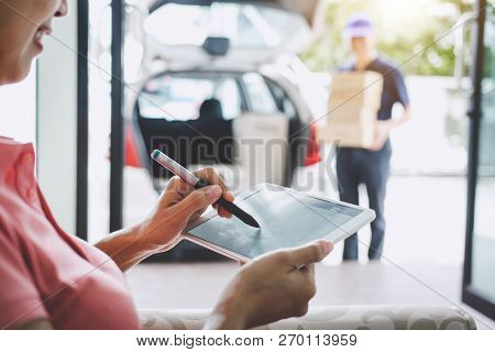 Woman Customer Appending Signature In Digital Tablet And Receiving A Cardboard Boxes Parcel From Del