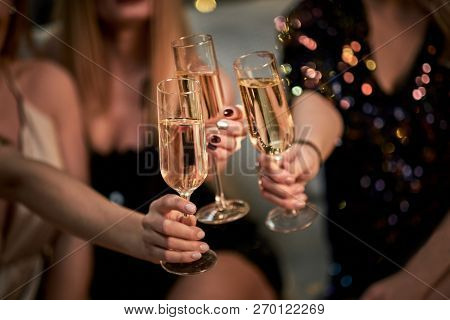 Female Friends Make Toast As They Celebrate At Party. Group Of Partying Girls Clinking Flutes With S
