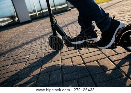 Close Up View Of Legs Of Man On Electric Scooter Outdoor.