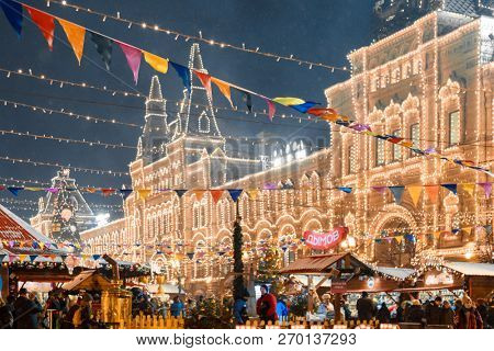Moscow, Russia, December 5, 2017: Tourists near illuminated facade of GUM Department store on Red Square during Christmas Fair in Moscow. Red Square is the central historical square in Moscow