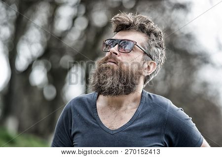 Man Bearded With Mustache Serious Face Confident Nature Background. Bearded Man With Sunglasses. Hip