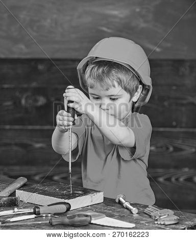 Kid Boy Holds Screwdriver Tool. Toddler On Busy Face Plays With Screwdriver At Workshop. Child In He
