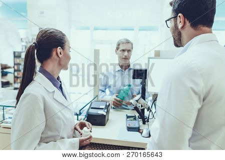 Pharmacists Working At Counter. Man Buys A Mineral Water. Female Pharmacist Holding A Bottle With Pi