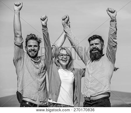 Company Of Three Happy Colleagues Or Partners Celebrating Success, Sky Background. Men With Beard In