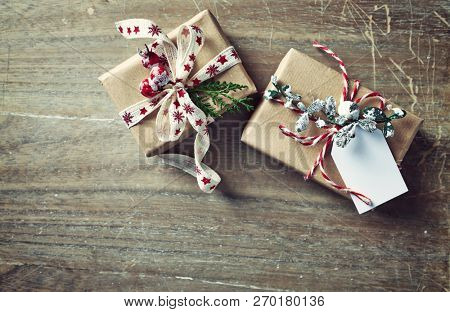 Christmas presents wrapped in brown paper on wooden background. Flatlay. Copy space