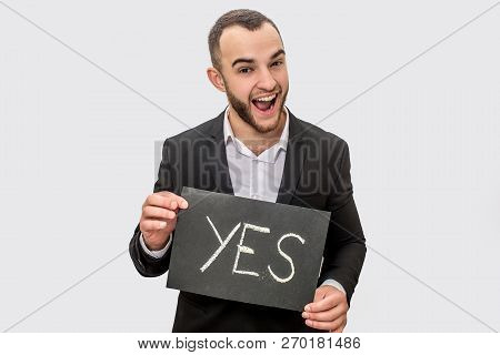 Happy Young Man In Suit Stands Nd Holds Tablet With Written Word Yes. Guy Look Straight On Camera. H