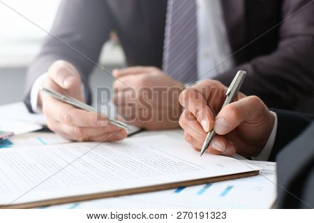 Male Arm In Suit And Tie Fill Form Clipped Pad With Silver Pen Closeup. Sign Gesture Read Pact Sale