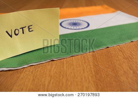 Voting Concept - Hand Written Voting Sticker On Indian Flag