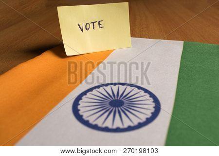 Voting Concept - Hand Written Voting Sticker On Indian Flag.