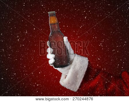 Closeup of Santa Claus holding a bottle of beer. Only hand and arm are visible. Horizontal format on a light to dark red spot background, with snow effect.
