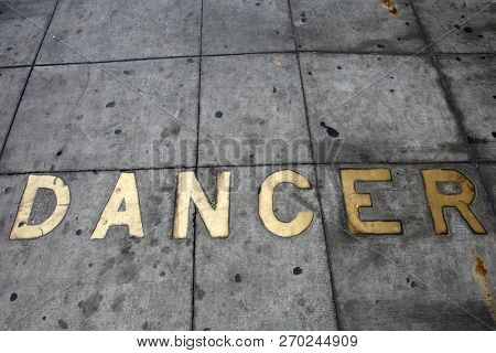 Metal Words in the Sidewalk. Old Metal Words imbedded in cement. The word DANCER written in Brass Letters Cemented into the sidewalk.